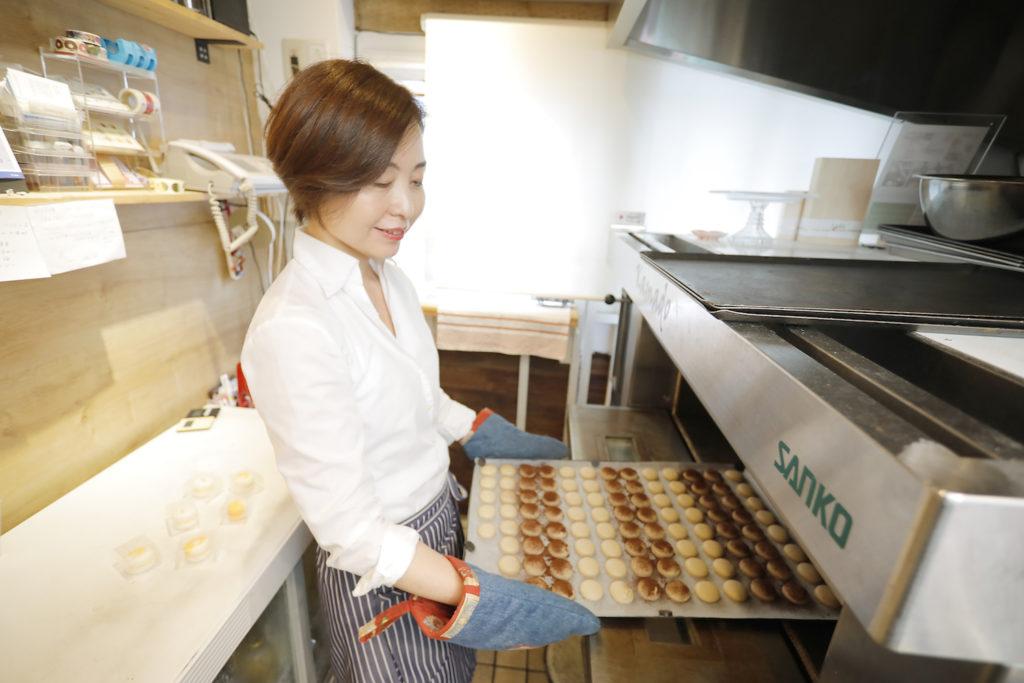オーブンからマカロンを取り出す川村祥子さん